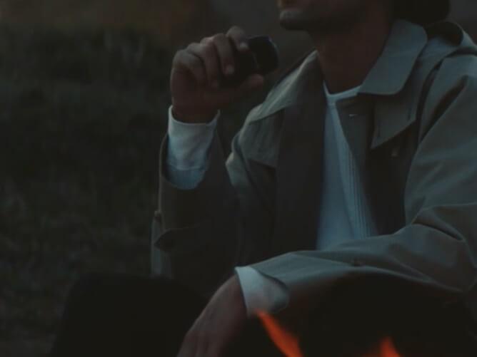 プルームエスを手に持った男性が焚火をしている